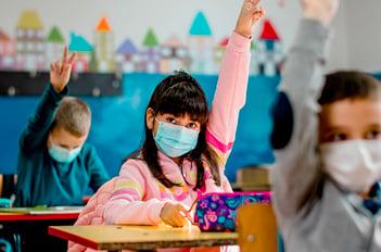 students in classroom raising hands